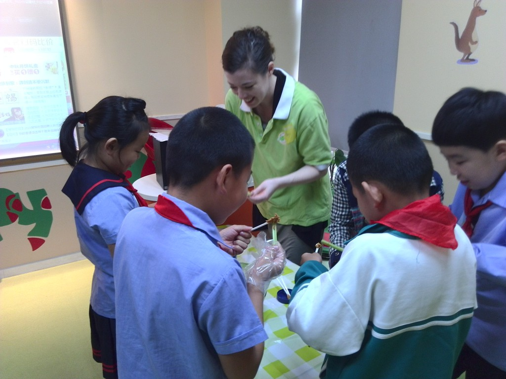 "Staff members teach Yongmei students how to make ""ants on a log"" -- celery topped with peanut butter and raisins."